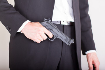 Man with gun, business suit, focus on the gun