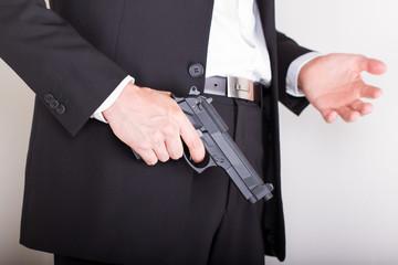 Man with gun, business suit, focus on the gun