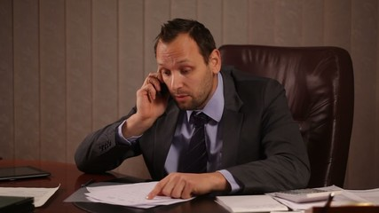 Angry boss talking on the phone in office