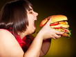 Hungry woman holding hamburger.
