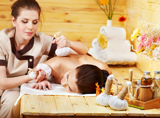Woman getting herbal ball massage.