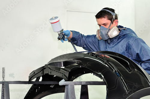 Man painting a black fender.