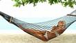 Beautiful woman suntanning in a hammock on a tropical beach