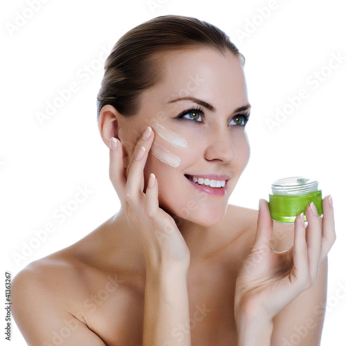 Happy smiling beautiful woman applying cream on the facem