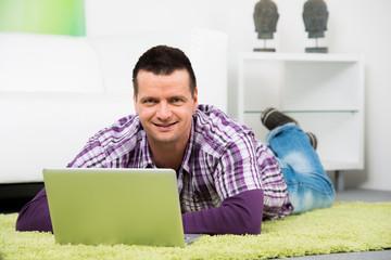 mann liegt mit seinem notebook auf dem teppichboden