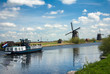 dutch landscape with tourist boat and windmills