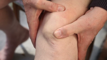 man moves his kneecap around