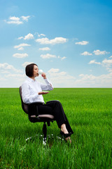 businesswoman with cup of coffee on the meadow