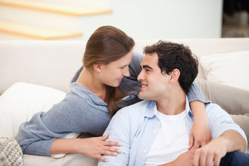 Couple embracing eachother while sitting a sofa