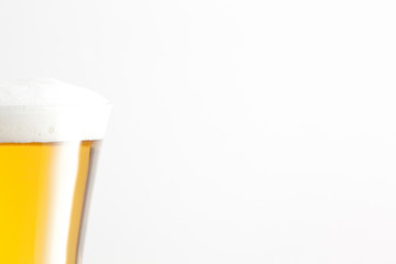Glass of beer and foam against a white background