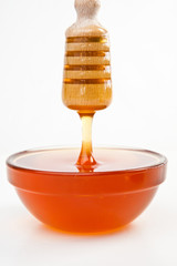Thin honey trickle dropping in full honey bowl