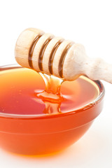 Honey sticky trickle dropping in a honey bowl