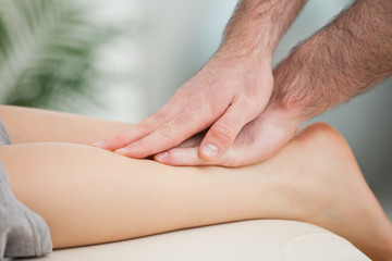 Physiotherapist massaging the calf of a woman