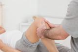 Man massaging the leg of a woman