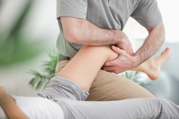 Man manipulating the leg of a woman while she is lying