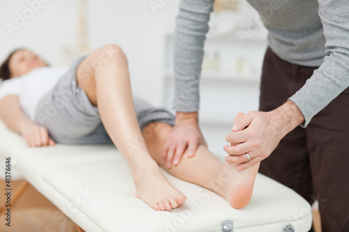 Physiotherapist stretching a barefoot