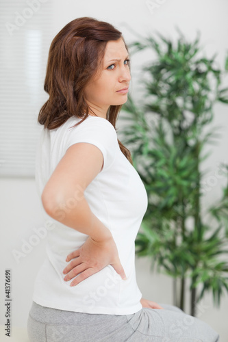 Woman touching her back while looking away