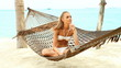Beautiful woman with long blonde hair sitting in a hammock