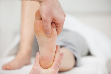 Practitioner placing his thumb on a foot