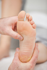 Doctor pressing the sole of a foot with his thumb