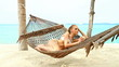 Attractive woman reclining in a hammock on a tropical beach