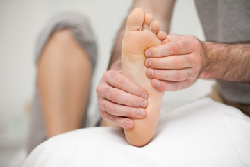 Chiropodist palpating the sole of the foot of a patient