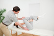 Physiotherapist pushing the leg of a woman on the side