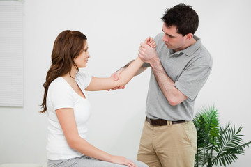 Serious practitioner touching the elbow of a woman