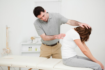 Physiotherapist looking at the spinal column of a woman
