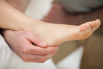 Ankle of a patient being held by a doctor