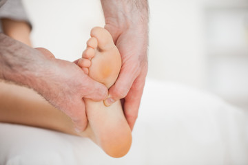 Physiotherapist using his fingers to massage a foot
