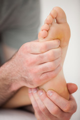 Hands of a practitioner holding a barefoot
