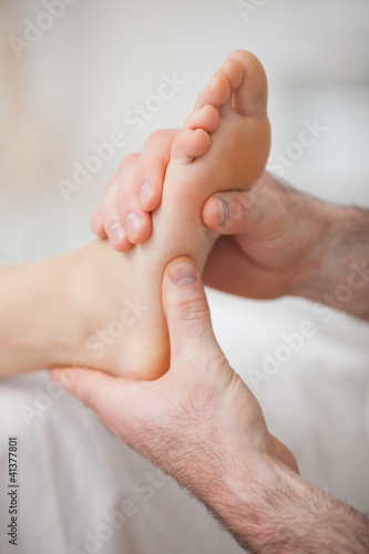 Foot receiving a massage by a physiotherapist