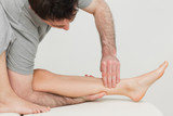 Serious osteopath massaging the shin bone of a patient