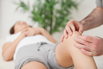 Knee of a woman being touched by a doctor