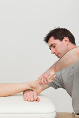 Serious practitioner holding the foot of a patient