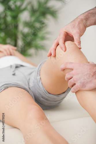 Fingers massaging the knee of a patient