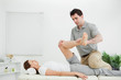 Chiropractor stretching the leg of his patient while holding it