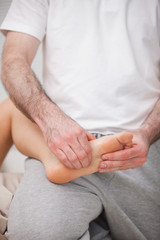 Reflexologist manipulating the sole of the patient