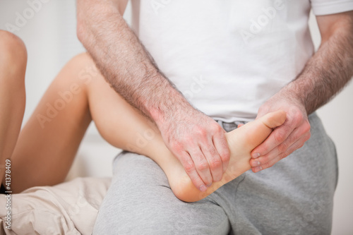 Reflexologist manipulating the foot of his patient while holding