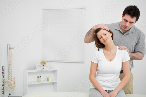 Doctor examining the neck of his patient while stretching it