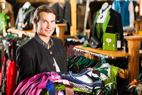 Mann kauft Tracht oder Dirndl in einer Boutique