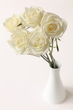 elegant bouquet of five white roses in vase on bright background