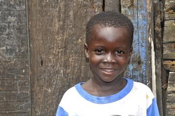 Afrikanischer Junge vor seinem Zuhause