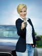 Pretty blonde woman proudly presents the key of her new car