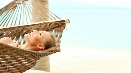 Cute woman lying on hammock on tropical beach