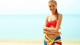Woman wearing pareo and bikini, standing at tropical beach poster