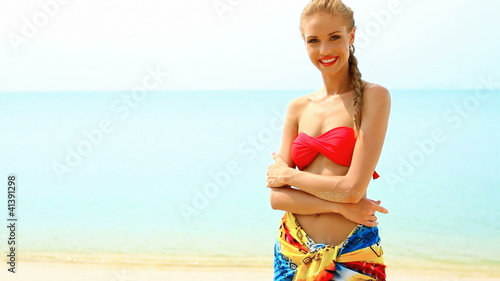 Woman wearing pareo and bikini, standing at tropical beach