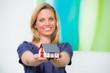 blonde junge frau präsentiert miniaturhaus