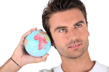Man listening into a globe
